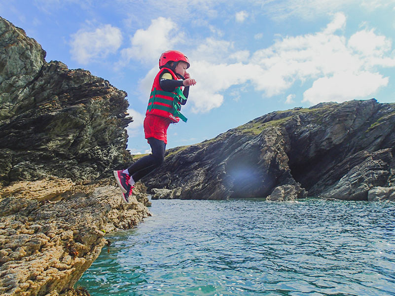 Small boy takes a jump into sea
