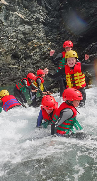 A group of kids enjoy traversing rocks on their Coasteering trip