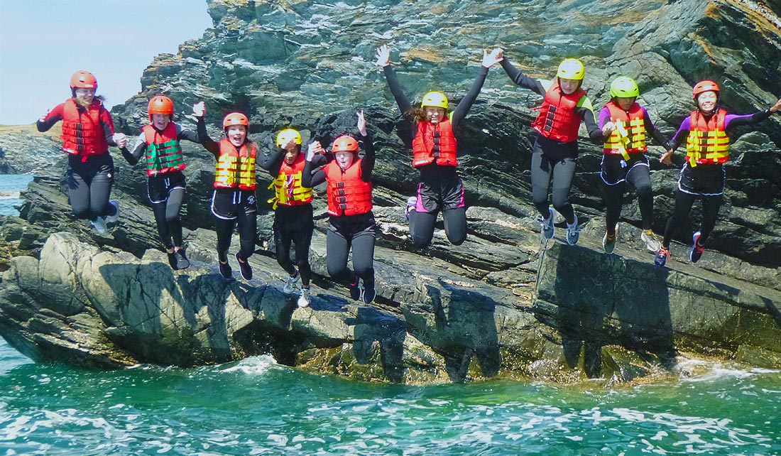 Large Coasteering group jumps together holding hands off a cliff edge