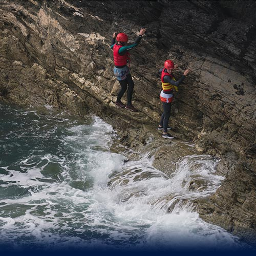 Two kid Coasteering on ledge avoiding water