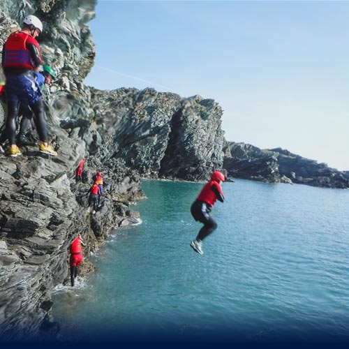 Womain performs Coasteering jump with arms folded